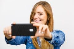 Mujer en la camisa del dril de algodón que toma la imagen del uno mismo con el teléfono Foto de archivo libre de regalías