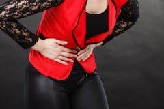Mujer en la camisa roja que tiene dolor de estómago foto de archivo