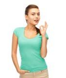 Mujer en la camiseta azul en blanco que muestra gesto aceptable Fotografía de archivo