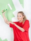 Mujer en la camiseta roja que muestra en el rodillo de pintura Imágenes de archivo libres de regalías