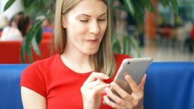Mujer en la camiseta roja que se sienta en café usando su smartphone, charlando con los amigos que comen las patatas fritas almacen de metraje de vídeo