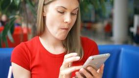 Mujer en la camiseta roja que se sienta en café usando su smartphone, charlando con los amigos que comen las patatas fritas almacen de video