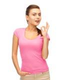 Mujer en la camiseta rosada en blanco que muestra gesto aceptable Imagen de archivo libre de regalías