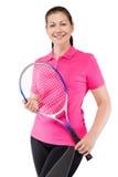 Mujer en la camiseta rosada que sostiene una estafa para el tenis en un blanco Imágenes de archivo libres de regalías