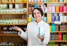 Mujer en la capa blanca que promueve mercancías del aditivo alimenticio en cartón en d Foto de archivo libre de regalías