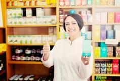 Mujer en la capa blanca que promueve mercancías del aditivo alimenticio en cartón en d Fotos de archivo