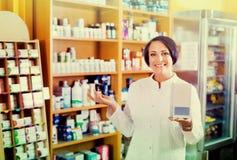 Mujer en la capa blanca que promueve mercancías del aditivo alimenticio en cartón en d Imagen de archivo libre de regalías