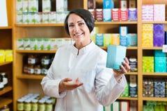 Mujer en la capa blanca que promueve mercancías del aditivo alimenticio en cartón en d Fotos de archivo libres de regalías