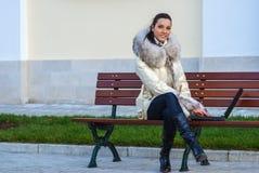 Mujer en la capa blanca que se sienta en banco imágenes de archivo libres de regalías