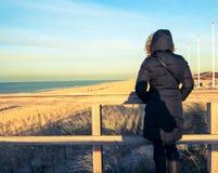 Mujer en la capa que mira el mar Fotos de archivo