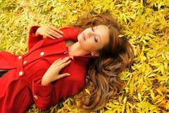 Mujer en la capa roja que miente en hojas de otoño Foto de archivo