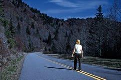 Mujer en la carretera en una noche del invierno Foto de archivo