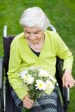 Mujer en la celebración de la silla de ruedas Foto de archivo libre de regalías