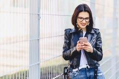 Mujer en la chaqueta de cuero en mensajería de los vidrios en el teléfono y sonrisas Imágenes de archivo libres de regalías