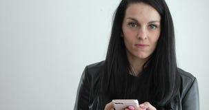 Mujer en la chaqueta de cuero negra que envía el mensaje en el teléfono celular almacen de metraje de vídeo