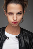 Mujer en la chaqueta de cuero que guiña y que engaña alrededor Fotografía de archivo libre de regalías