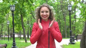 Mujer en la chaqueta de cuero roja que mira la cámara y asombrosamente sorprendida, al aire libre sobre parque del verano almacen de metraje de vídeo