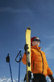 Mujer en la chaqueta del invierno que detiene a Ski Against Blue Sky Foto de archivo