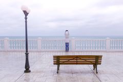 Mujer en la chaqueta y la capilla blancas en terraza hermosa con la opinión del mar sobre la costa Visión posterior fotografía de archivo libre de regalías