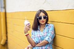 Mujer en la ciudad en el fondo de una pared amarilla, sosteniendo el batido de leche, jugo fresco en vidrios, camisa que lleva co Fotografía de archivo