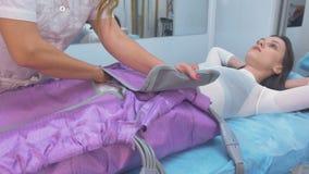 Mujer en la clínica para el tratamiento del procedimiento de la terapia de la presión Preparación al procedimiento con un doctor almacen de metraje de vídeo