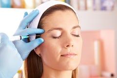 Mujer en la clínica de la belleza que consigue la inyección del botox Imagenes de archivo