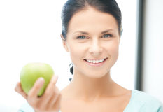 Mujer en la cocina con una manzana Imagenes de archivo