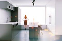 Mujer en la cocina gris con una barra, vista lateral del desván Fotografía de archivo