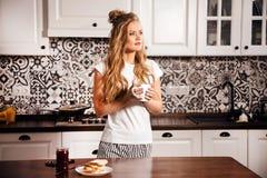 Mujer en la cocina en la mañana imagen de archivo