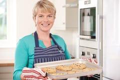 Mujer en la cocina que detiene a Tray With Home Baked Cookies Foto de archivo libre de regalías