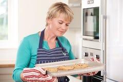 Mujer en la cocina que detiene a Tray With Home Baked Cookies Fotografía de archivo libre de regalías