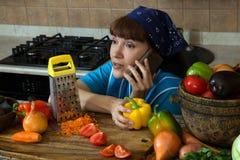 Mujer en la cocina que habla en el teléfono Imagenes de archivo