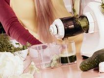 Mujer en la cocina que hace el jugo vegetal del smoothie Imagen de archivo