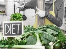 Mujer en la cocina que tiene verduras verdes de la dieta Imagen de archivo libre de regalías
