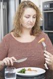 Mujer en la comida de Fed Up With Eating Healthy de la dieta Fotos de archivo libres de regalías