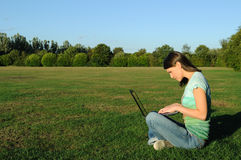 Mujer en la computadora portátil afuera Fotos de archivo