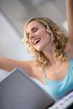 Mujer en la computadora portátil con los brazos para arriba Fotografía de archivo