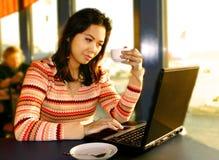 Mujer en la computadora portátil en salón Imagen de archivo libre de regalías