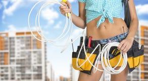 Mujer en la correa de la herramienta que sostiene el cable eléctrico Fotos de archivo libres de regalías