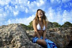 Mujer en la costa que mira en horizonte del océano en acantilado de la roca por la orilla de mar en abrigo de la playa de los sar Imagen de archivo libre de regalías
