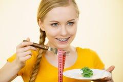 Mujer en la dieta que sostiene la placa con lechuga Foto de archivo