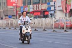 Mujer en la e-bici con signings de la tienda en el fondo, Pekín, China Fotos de archivo