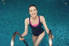Mujer en la escalera de la piscina en el gimnasio La chica joven parece feliz, de moda y apta en una pieza Fotografía de archivo