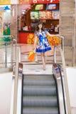Mujer en la escalera móvil Foto de archivo libre de regalías