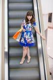 Mujer en la escalera móvil foto de archivo