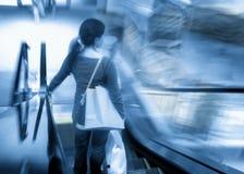 Mujer en la escalera móvil Imagenes de archivo