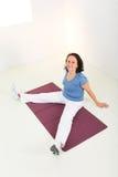 Mujer en la estera de la yoga Imagen de archivo libre de regalías