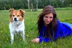 Mujer en la hierba con su perro Imagen de archivo