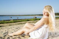 Mujer en la indulgencia blanca del vestido en la arena Imagenes de archivo