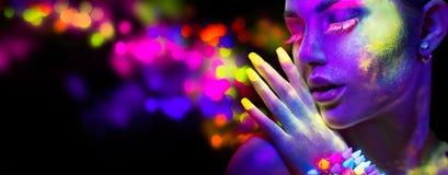 Mujer en la luz de neón, retrato del modelo hermoso con maquillaje fluorescente